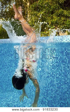 Happy smiling underwater child jumps to swimming pool, beautiful little girl swims and having fun
