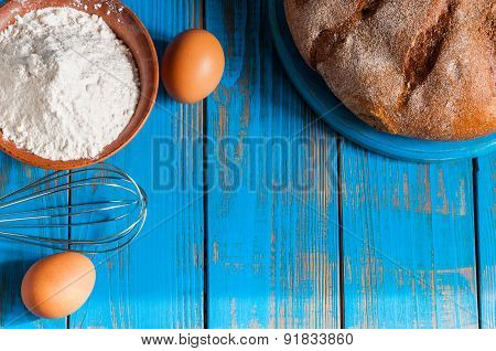 Baking cake in rural kitchen - dough recipe ingredients eggs, flour, butter and whisk on vintage woo