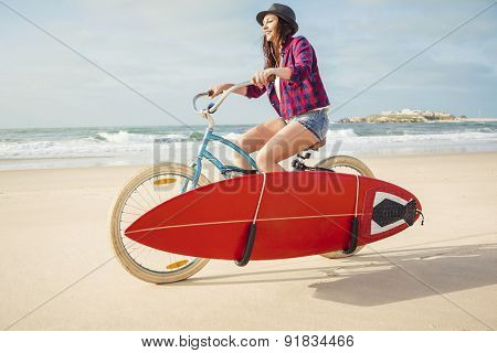 Surfer young woman riding her bicycle on the beach