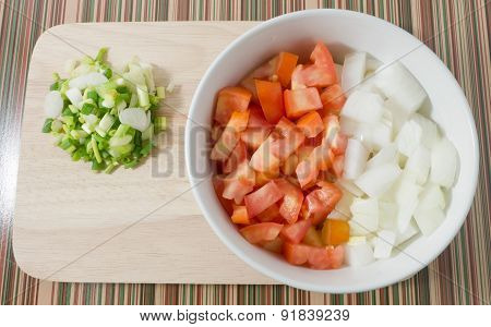 Cutting Board With Chopped Tomatoes, Onions And Spring Onions