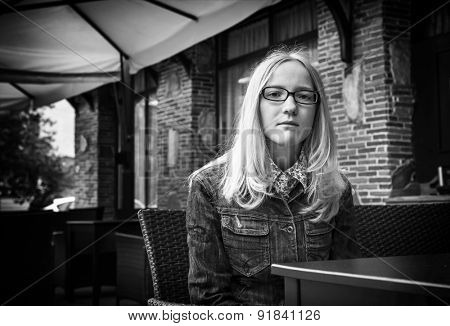Black and white portrait of young blond girl in the street cafe