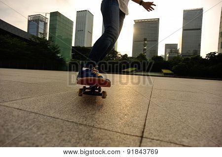 woman skateboarder legs skateboarding at sunrise city