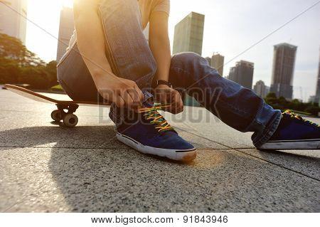 skateboarder hands tying shoelace at skate park