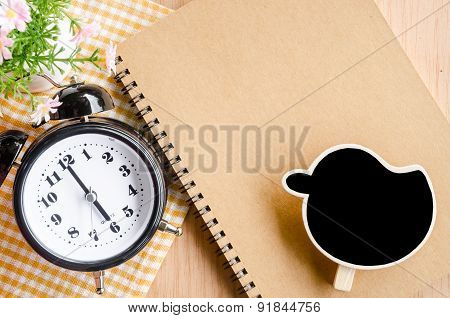 Time management concept: vintage alarm clock, blank black tag and diary.