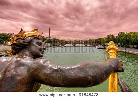 View of Seine river and Eiffel Tower on background under cloudy sky from Alexander the III bridge in Paris, France.