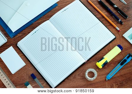 Office Supplies Arranged Around Notebook On Desk