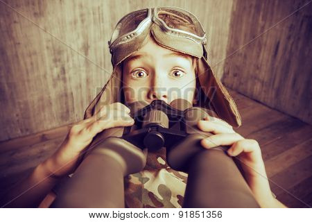 Boy plays the pilot, holding binoculars and surprised. Childhood. Fantasy, imagination. Retro style, sepia.