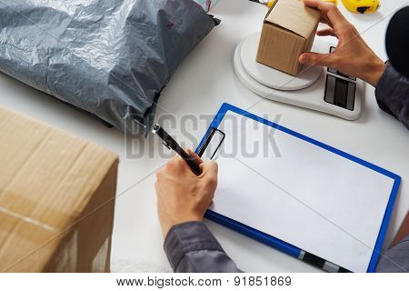 Post worker weighs the parcel