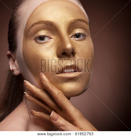 Girl With Gold Fashion Make Up On Brown Background