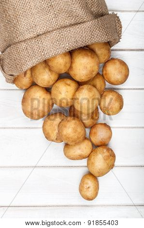 New Potatoes In A Burlap Bag On A White Wooden Background