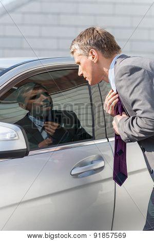 Businessman adjusting tie while looking in car window