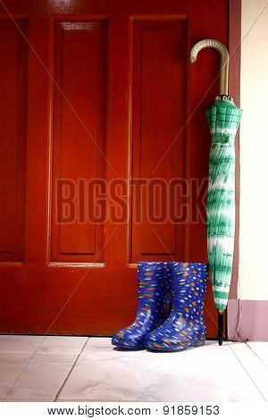 Umbrella and rubber or rain boots by the door