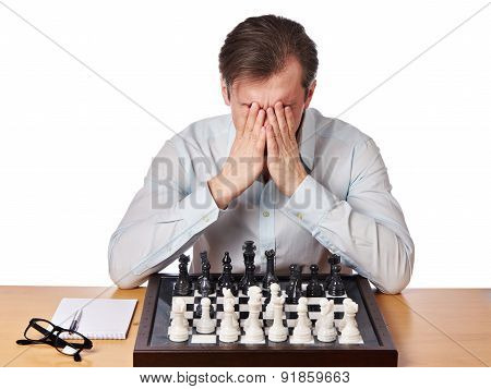 Man Covered Face With His Hands In Heavy Chess Game