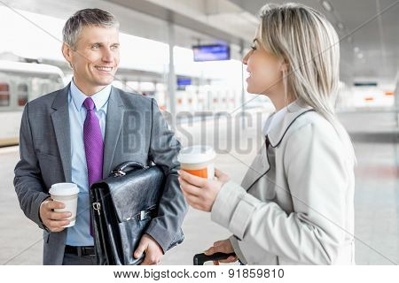 Businessman and businesswoman with coffee cups talking at railroad platform