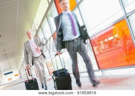 Middle aged businessmen with luggage rushing on railroad platform