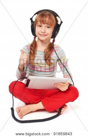Little girl enjoying music listening in headphones