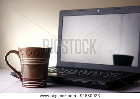 Coffee mug and a laptop computer