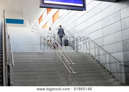 Rear view of businesspeople with luggage moving upstairs in railroad station