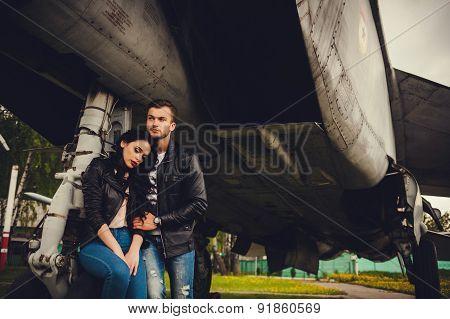 Stylish Couple Hugging Near The Aircraft