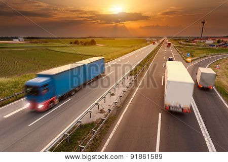 Many Trucks In Motion Blur On The Highway At Sunset
