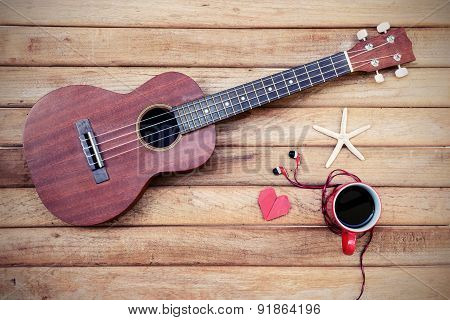 Cup Of Coffee With Ukulele On Old Wooden Background