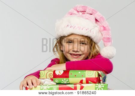 A little girl in a studio environment with presents missing her two front teeth