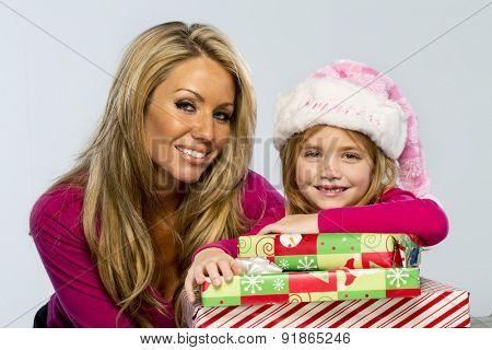 A mother and daughter pose in a studio environment with presents