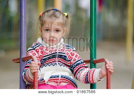 Upset Four-year Girl Riding On A Swing