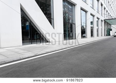 Empty road nearby office building