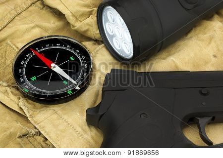 Handgun, Compass And Led Tourchlight On The Backpack