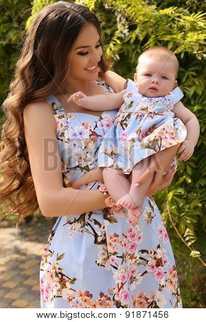 beautiful mother with long dark hair posing with her little cute baby