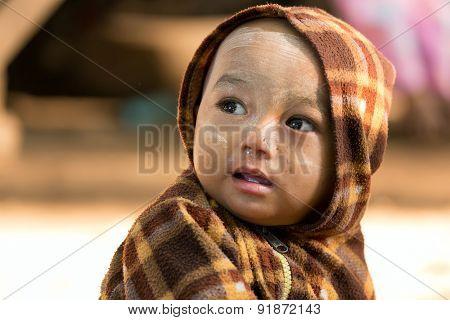 BAGAN, MYANMAR, JANUARY 24, 2015: Portrait of a Burmese little child in a street of the old Bagan village in Myanmar (Burma)