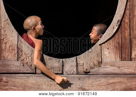NYAUNG SHWE, MYANMAR, JANUARY 27, 2015: Two young novice buddhist monk are talking and laughing at a window of the Shwe Yaunghwe Kyaung monastery in Nyaung Shwe, Myanmar (Burma).