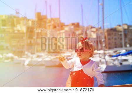cute little girl travel in the port