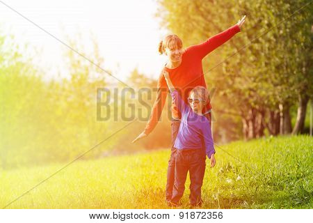 mother and son playing in summer park