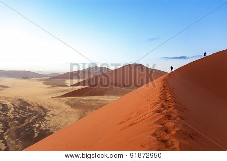 People walking on beautiful sunrise dunes of Namib desert, Sossusvlei, Namibia, South Africa