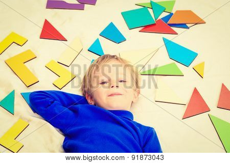 happy little boy with puzzle toys on white