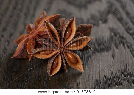 anise stars on old oak table close up photo