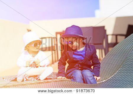 cute little boy and toddler girl talking on luxury terrace