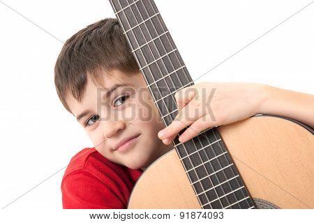 Smiling Boy Hugging An Acoustic Guitar