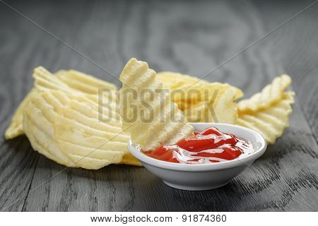 rippled organic chips wit tomato sauce on wooden table