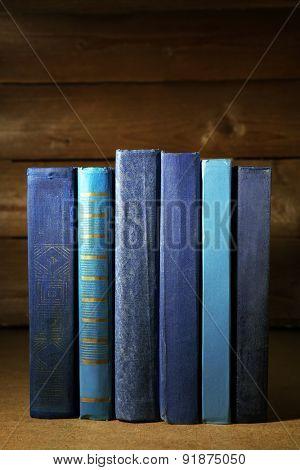 Old blue books on shelf, close-up, on dark wooden background
