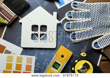Construction instruments, plan and brushes on house plan background
