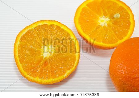 Halved Oranges On A White Cardboard