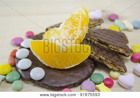 Fresh Orange, Biscuits And Colorful Bonbons