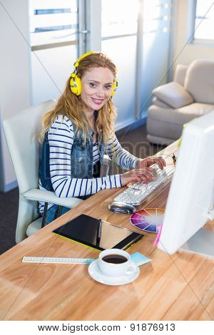Smiling designer typing on keyboard and listening music in the office