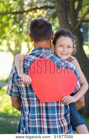 Father and daughter hugging in the park on a sunny day