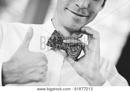 Close Up Handsome Businessman Fixes His Bow Tie Smile And Giving Hands Up