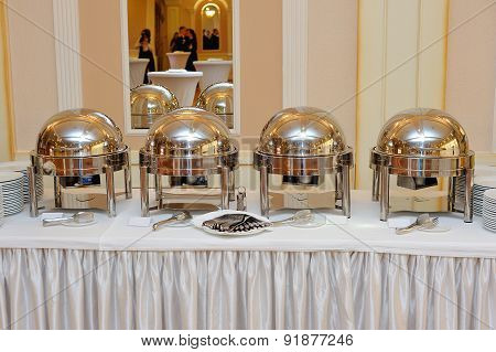 Four Closed Stainless Steel Cloche On Wooden Table On Restaurant