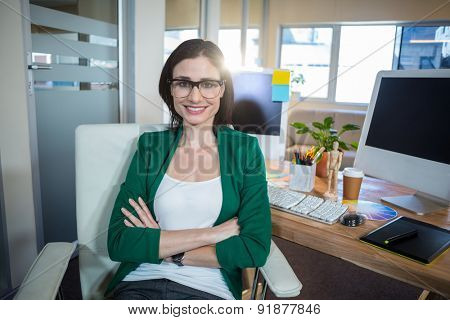 Smiling brunette sitting at her desk arms crossed in the office